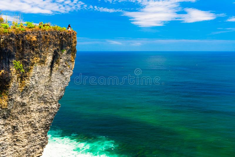 Young travel girl sits on the edge of a cliff on background amazing nature landscape tropical island Bali, Indonesia royalty free stock images