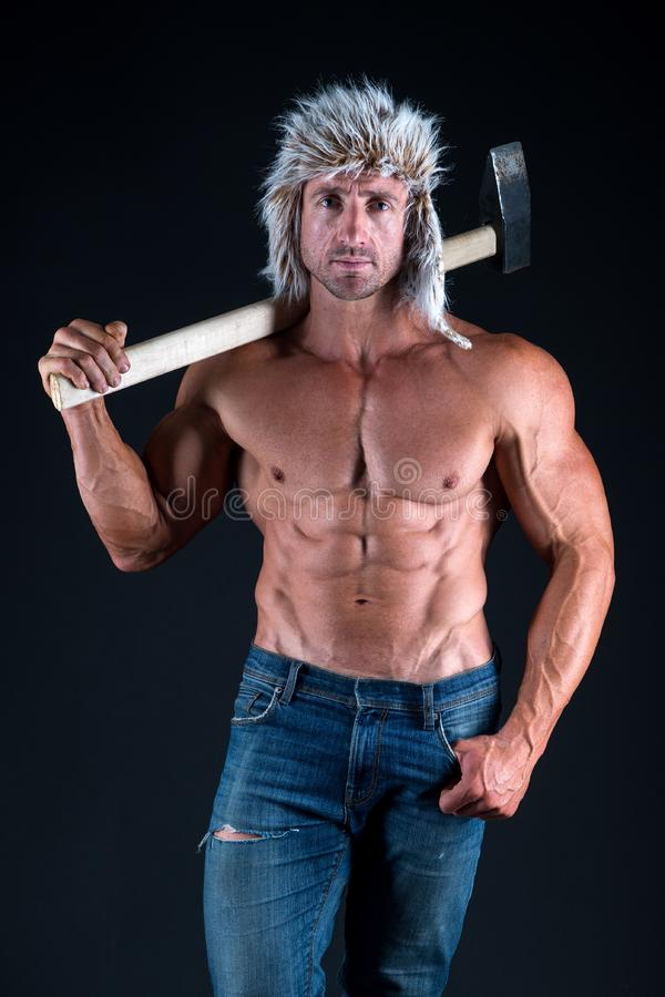 Success. man with sexy bare torso in jeans. strong bodybuilder with sexy bare torso. man in hat with fit torso hold royalty free stock images