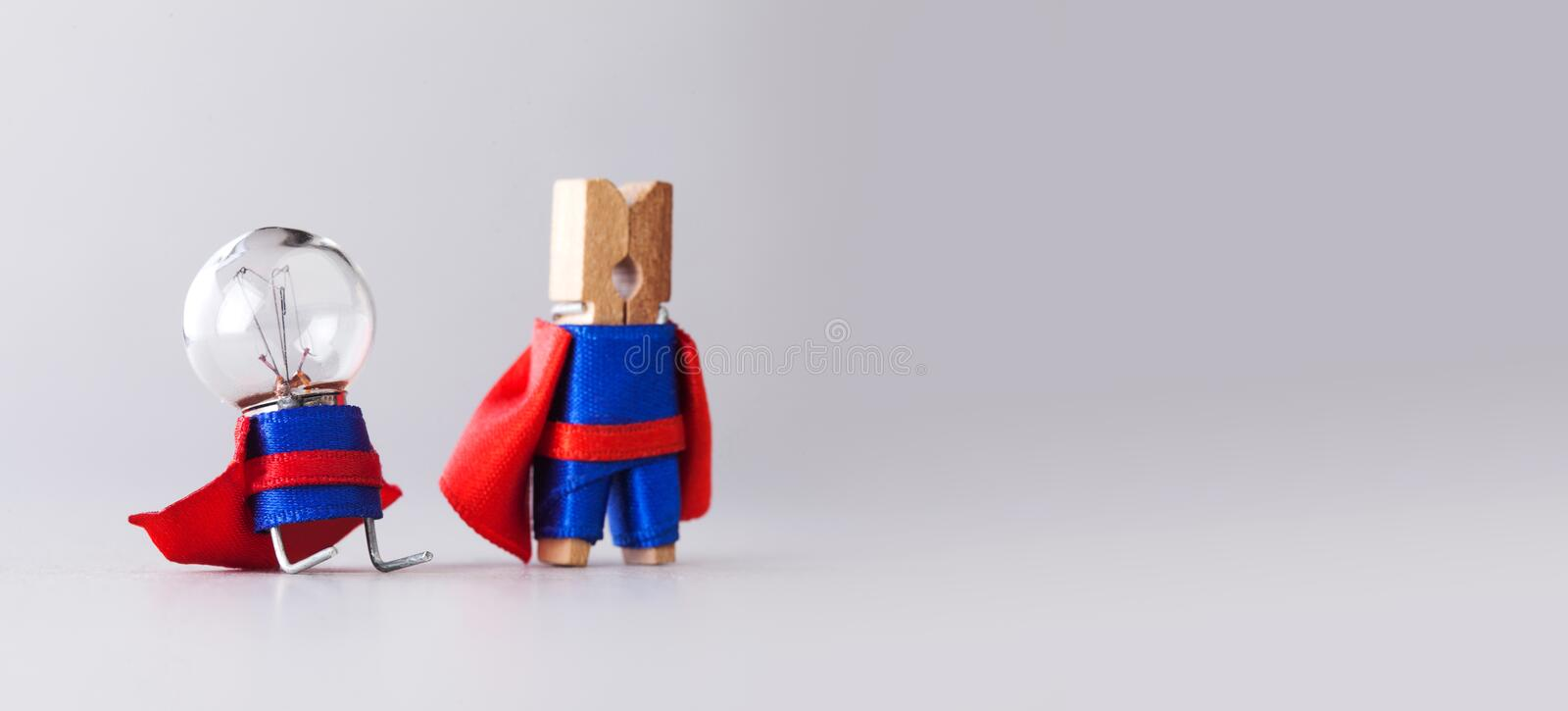 Success management creative concept. Super heroes team clothespin and light bulb, funny toy characters in blue suit and. Red cape. Gray background copy space stock image