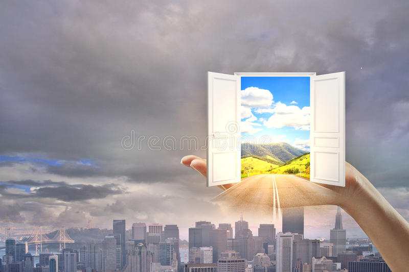 Success and opportunity concept. Hand holding abstract open door with bright landscape view on dull city background. Success and opportunity concept stock photography