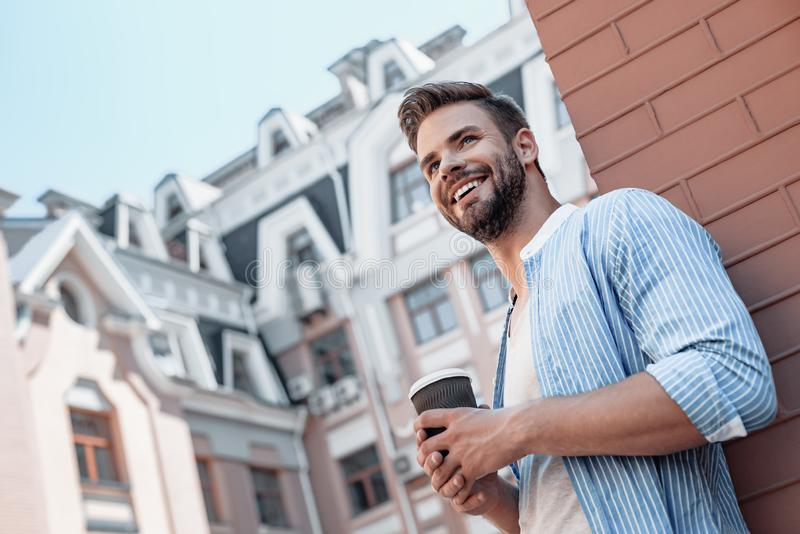 Success is peace of mind. Portrait of confident brown-haired man holding coffee cup and smiling aside while walking royalty free stock photos