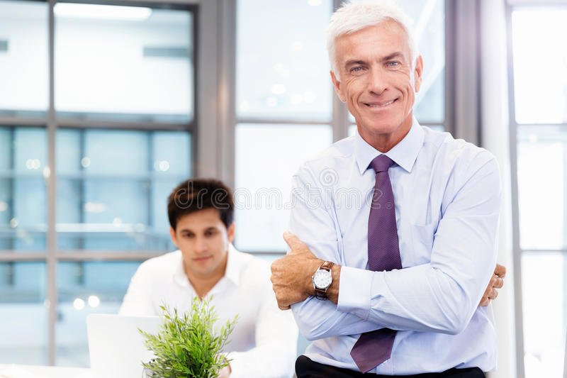Success and professionalism in person. Businessman standing in office smiling at camera royalty free stock photos