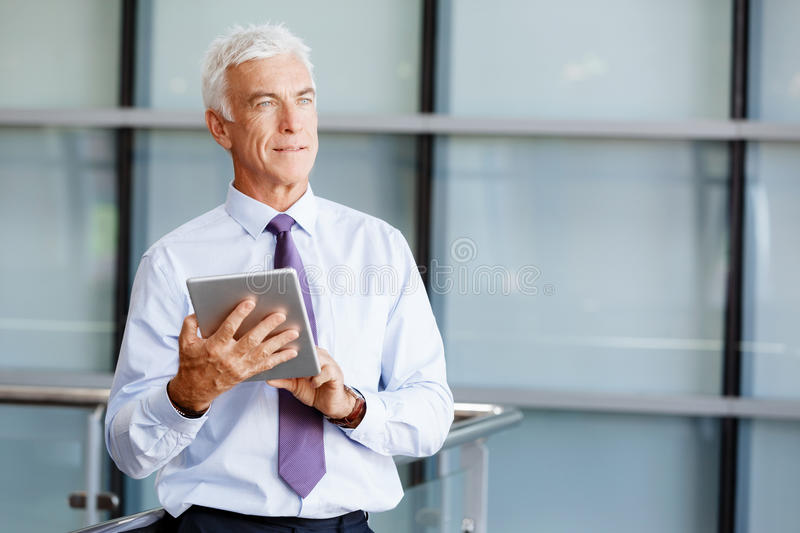 Success and professionalism in person. Businessman standing with tablet smiling at camera stock images