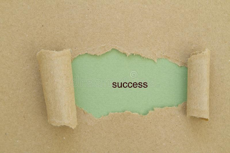 Success. Word written under torn paper concept stock image