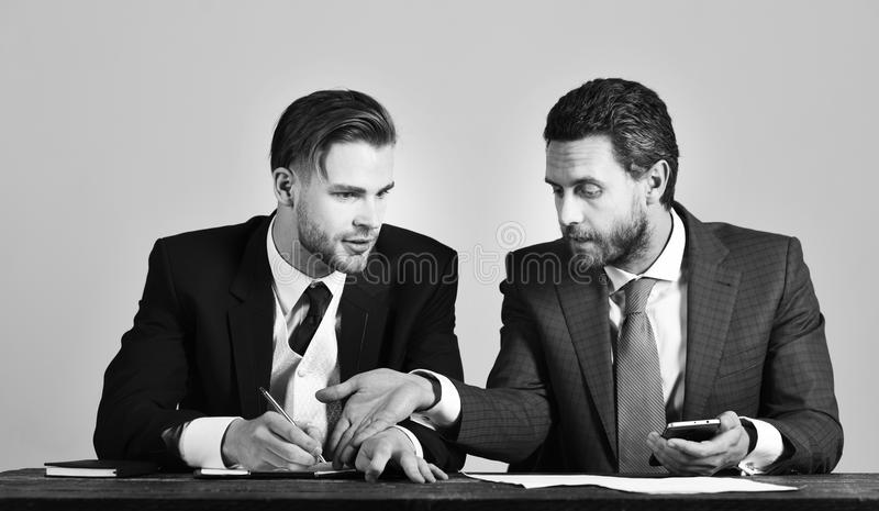 Success, support, partnership concept. Businessman consults with financial expert having serious face. Expert holds smartphone and explains new business plan stock photos