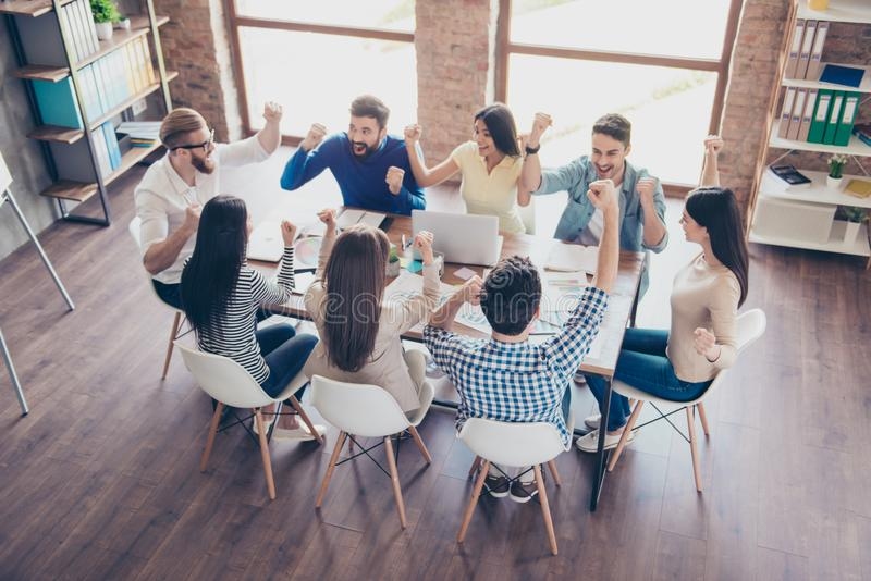 Success and team work concept. Top up of team of business partners with raised up hands in light modern workstation, celebrating stock photography