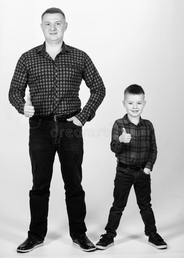 Success. thumb up gesture. happy family. fathers day. childhood. parenting. father and son in red checkered shirt. Little boy with dad man. Wild West is his royalty free stock images