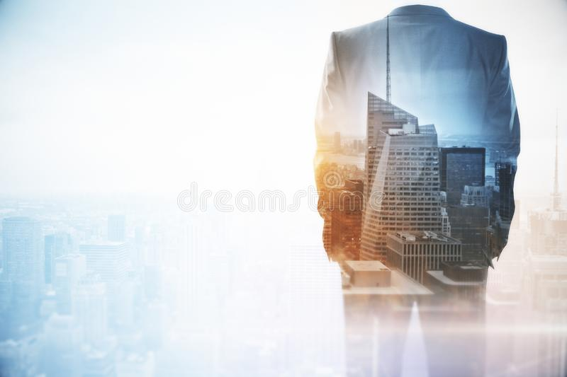 Success and tomorrow concept. Businessman standing on abstract city background with copy space. Double exposure royalty free stock images