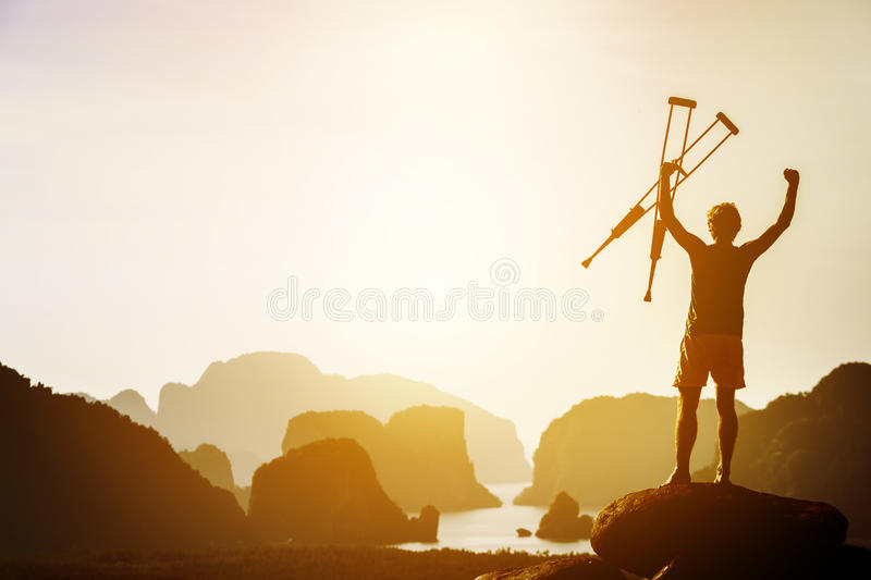 Success or winner concept with disabled man and crutches. Man with crutches stands in winner pose with rised hands on mountains and islands background. Space for royalty free stock photography
