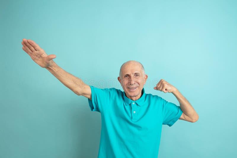 Caucasian senior man`s portrait isolated on blue studio background stock photography