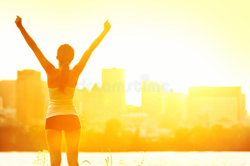 Success winner woman. Standing with arms up joyful after outdoors workout. Half silhouette on sunny warm summer day with city skyline in background, From royalty free stock photos