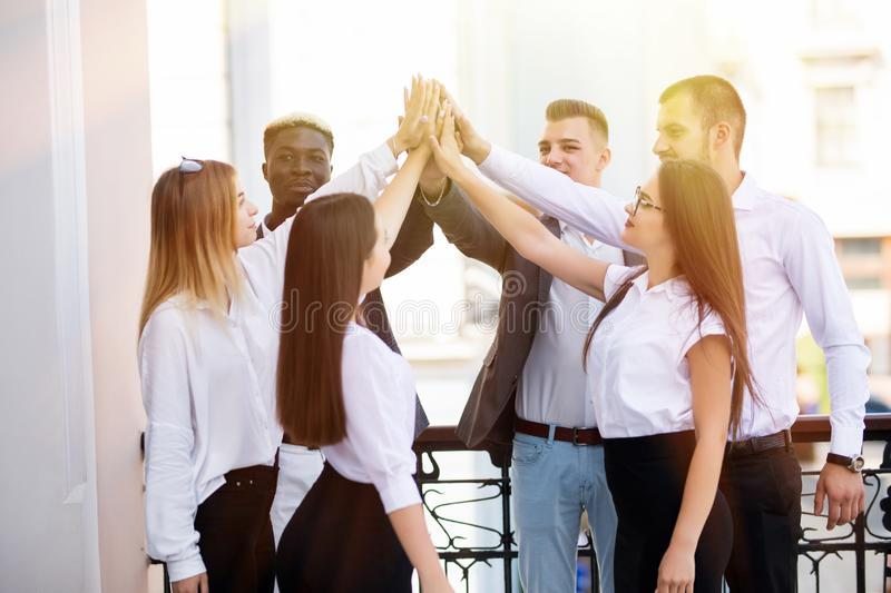 Success and winning concept. Happy business team giving high five in office stock photography
