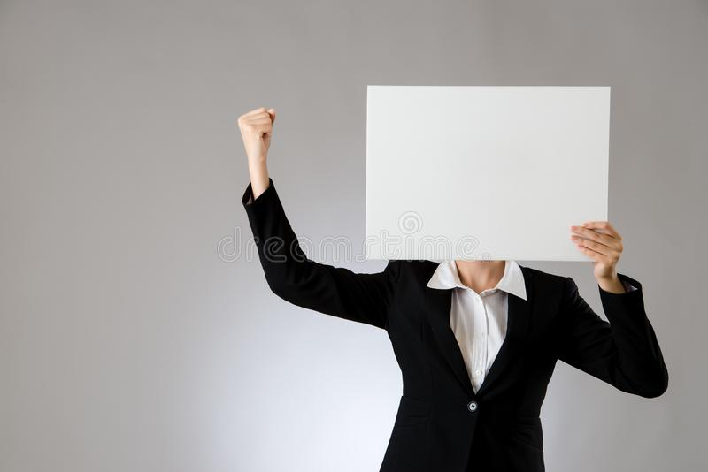 Success woman hand arm up to celebrate. Winning a project and holding a empty sheet board. isolated on gray background. mixed race asian chinese model stock photos