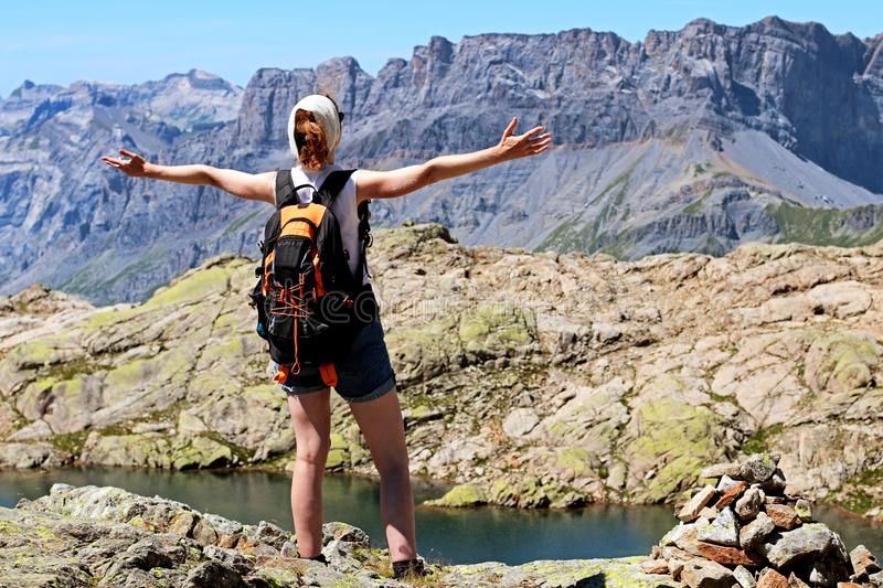 Success woman reaching goal at summit in Chamonix. Happy hiker reaching life goal, enjoying and greeting rich nature on the top of a mountain in Mont Blanc royalty free stock image