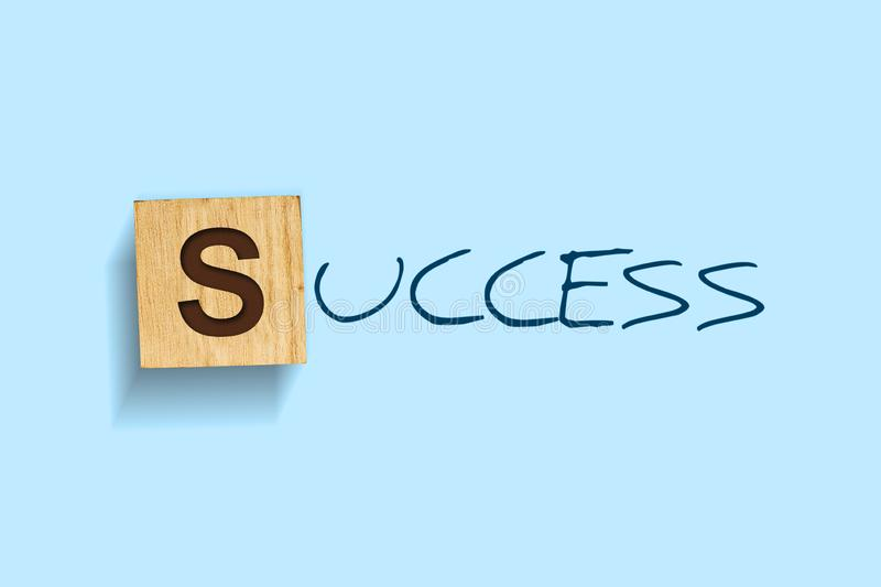 Success. Words written on a wooden block. Blue background. Isolated. Business stock image