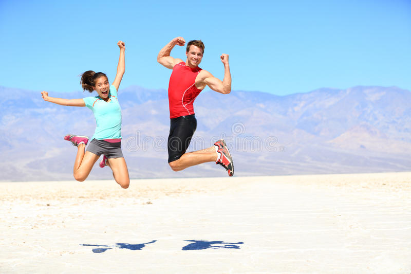 Success - young runners jumping. Excited celebrating and cheering happy and energetic on dramatic desert landscape. Young joyful sporty fitness interracial fit stock photography