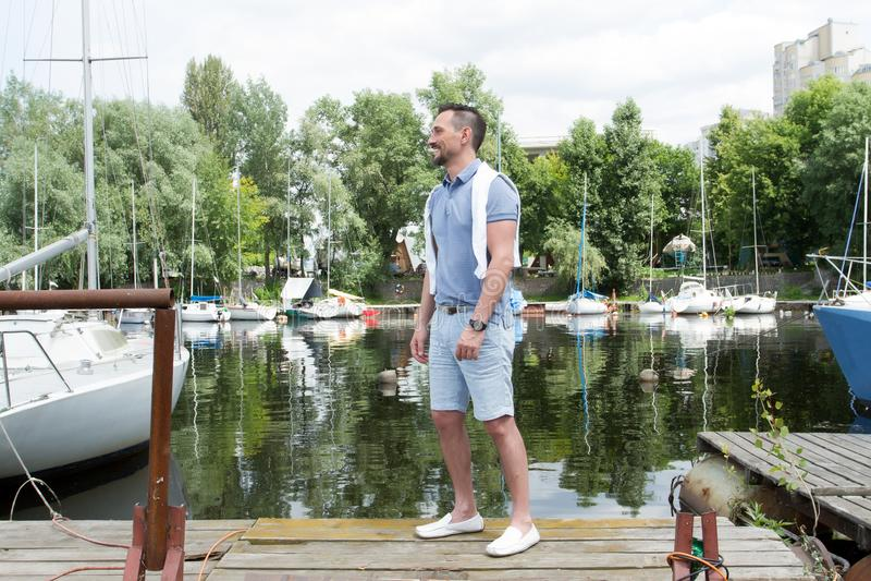 Successeful人去他的在河海湾的游艇 可爱的人在有游艇的海小游艇船坞 航行的夏令时年轻人 免版税库存图片