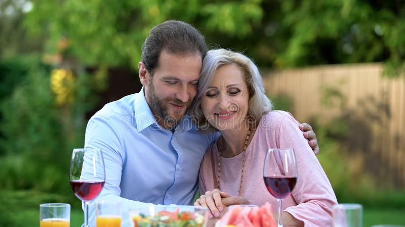 Successful adult son thanking mother for upbringing, emotional embrace love stock image