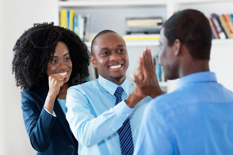 Successful african american business team gives high five stock photo