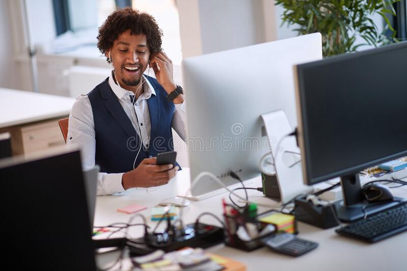 Successful african american businessman holding mobile phone call. Young business people in office. Successful african american young businessman holding mobile royalty free stock image