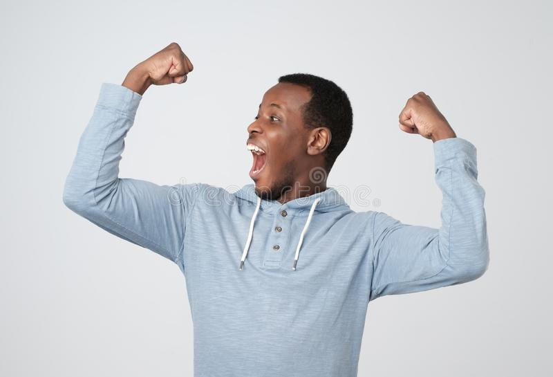 successful african man winning, fists pumped celebrating success isolated grey wall background. Life perception, achievement stock photo