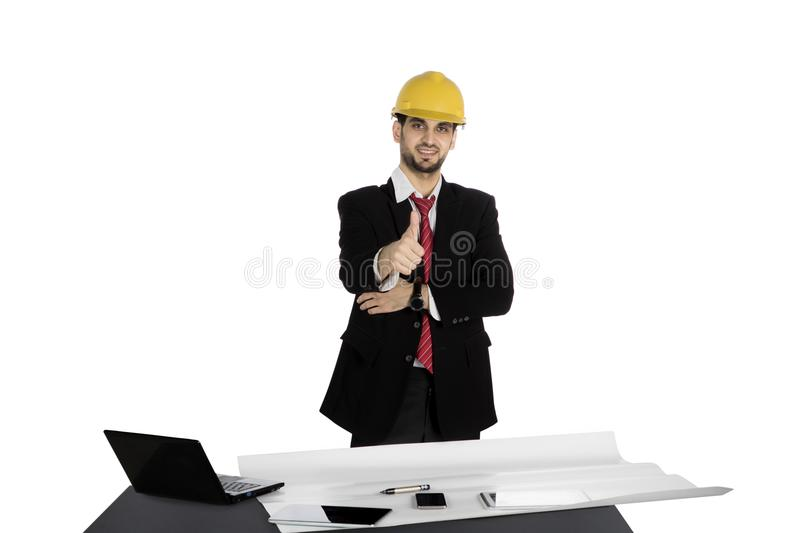 Successful architect showing thumb up. Successful Arabian architect showing thumb up while wearing helmet with blueprint, laptop, and tablet computer on desk royalty free stock images