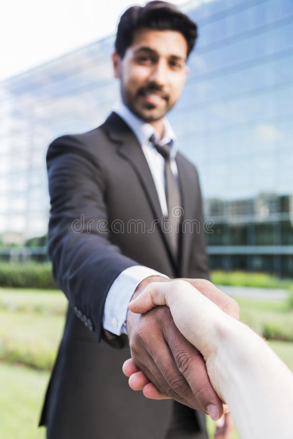 Successful arabic businessman or worker shaking hands with person. Arabic serious smiling happy successful positive businessman or worker in black suit with royalty free stock image