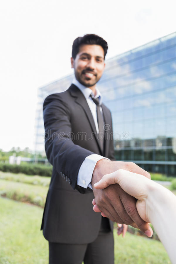 Successful arabic businessman or worker shaking hands with person. Arabic serious smiling happy successful positive businessman or worker in black suit with stock images