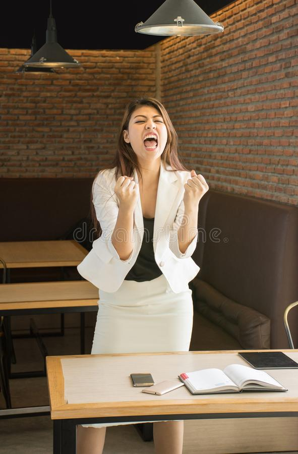 Successful Asian business woman with arms up stock photography
