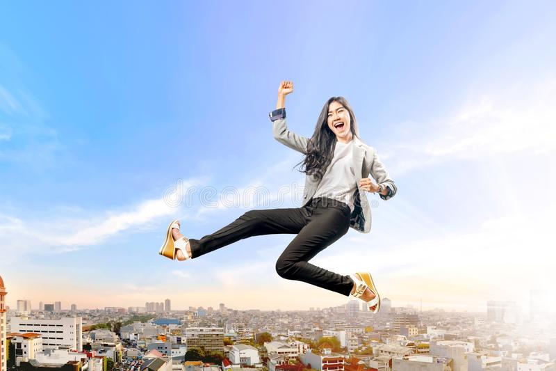 Successful asian business woman jumping high stock image