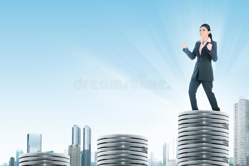 Successful asian business woman standing on the highest silver coins stock images