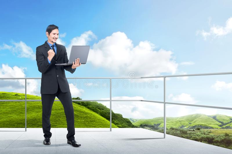 Successful asian businessman standing with laptop on the terrace. With green landscapes view and blue sky background royalty free stock photos