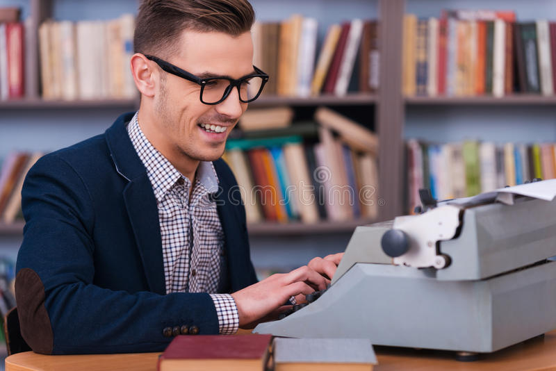 Successful author. Side view of happy young author typing something at the typewriter and smiling while sitting at his working place with bookshelf in the stock photo