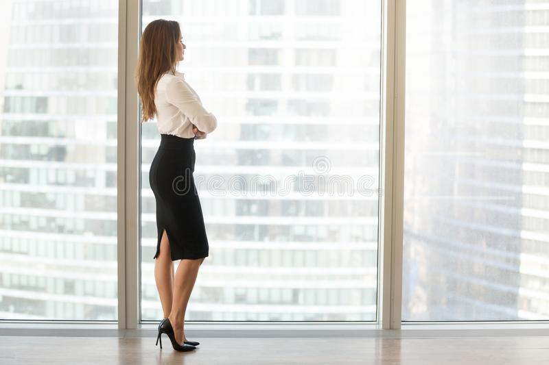 Successful beautiful businesswoman standing looking out of windo. Successful businesswoman standing looking out of window enjoying city view and contemplating stock photography