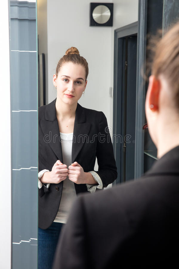 Successful beautiful young woman with winning body language standing. In front of her mirror, getting ready for business from home, looking at her reflection in stock photos