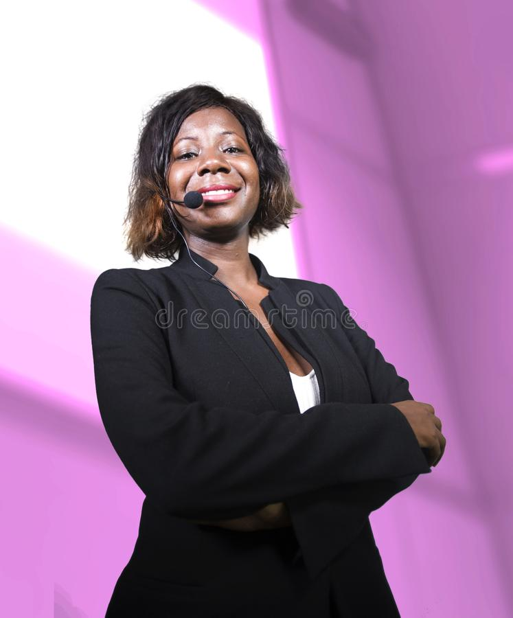 Successful black African American business woman with headset speaking in auditorium at corporate training event or seminar giving. Young attractive and royalty free stock photography