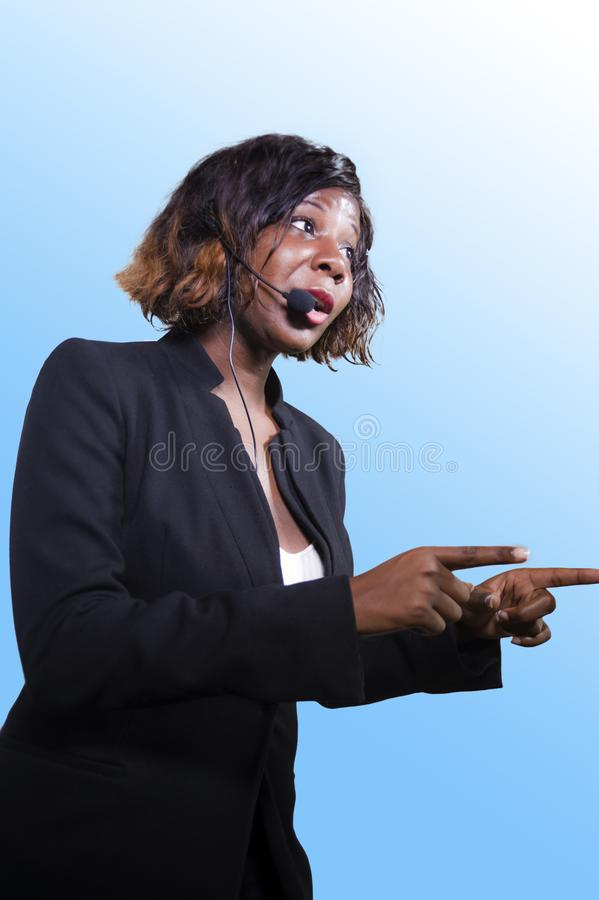 Successful black afro American business woman with headset speaking in auditorium at corporate training event or seminar giving. Young attractive and successful royalty free stock images