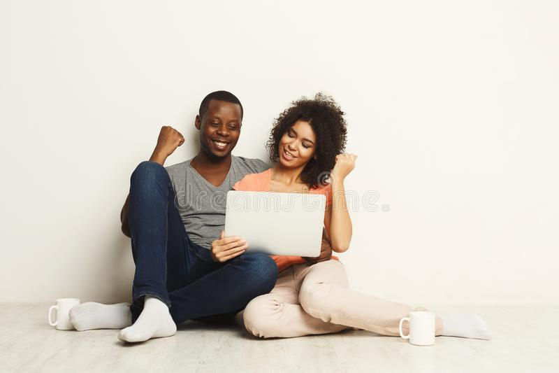 Successful black couple winning in online game. Happy african-american couple gambling online on laptop and winning. Succuess and online gaming concept, copy stock image