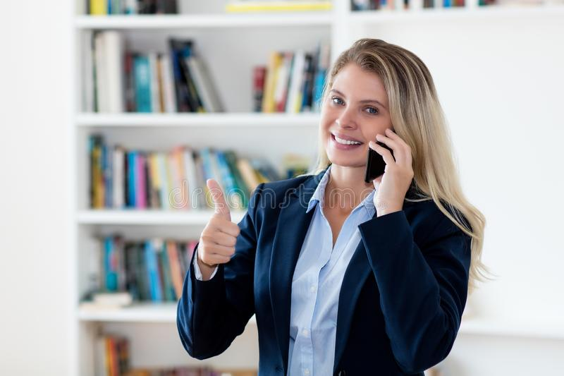 Successful blond businesswoman talking with client at phone royalty free stock photos