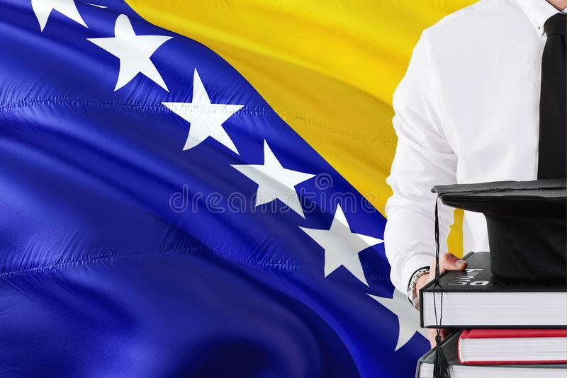 Successful Bosnian student education concept. Holding books and graduation cap over Bosnia Herzegovina flag background.  stock images