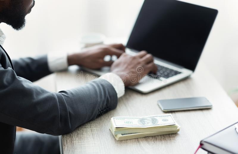 Successful business concept. Black businessman using laptop analyzing financial data. royalty free stock photography
