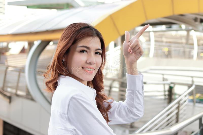 Successful business concept. Portrait of attractive young Asian businesswoman looking confident and smile at urban building backgr royalty free stock photo