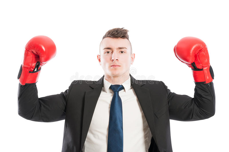 Successful business man lifting arms up as a champion. Or winner. Confident entrepreneur wearing red boxing gloves concept stock photography