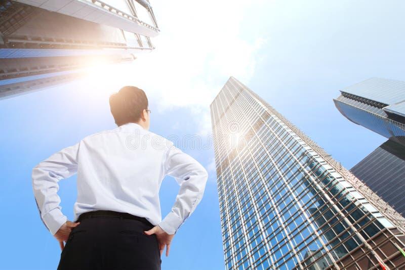 Successful business man outdoors Next to Office Building. Happy successful business man outdoors Next to Office Buildings with cityscape and sky, hong kong, asia stock photo
