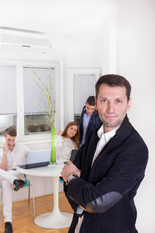 Successful business man standing with his staff colleagues in ba royalty free stock image