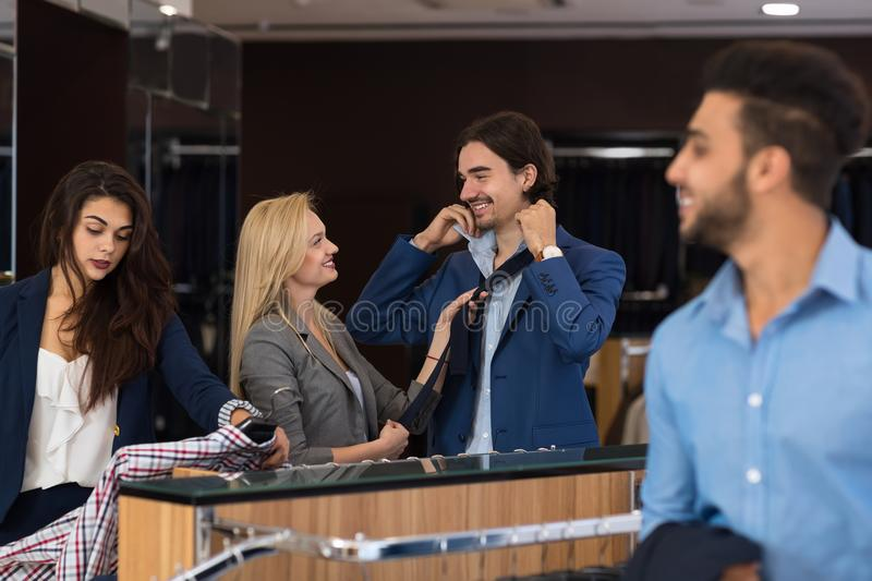 Successful Business Men Buying New Clothes In Modern Suits Shop, Female Assistants Helping stock photos