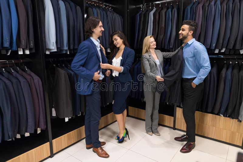 Successful Business Men Choosing New Suits With Attractive Female Sellers Offering Elegant Clothes stock image