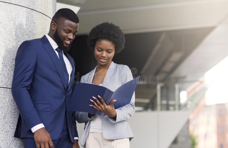 Successful business partners checking financial reports outdoors stock image