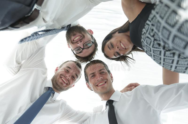Successful business people with arms around each other`s shoulders. stock images