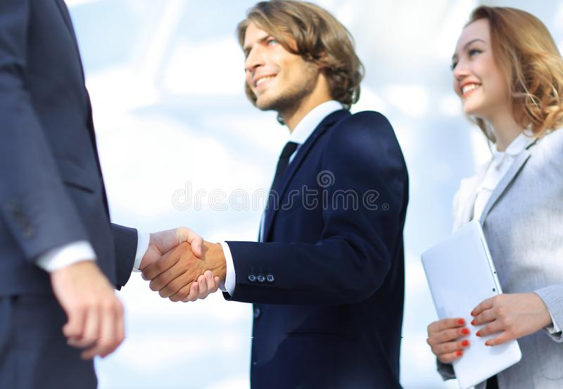 Successful business people handshake greeting deal concept. Close-up shot of businessmen shaking hands in the office stock photography